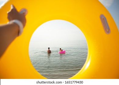 close-up pf woman hand holding th yellow rubber ring and look to the cirkle toe the family swimming in the sea.