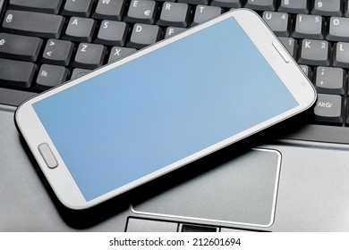 Closeup of a phablet on a laptop as concept of portable technology