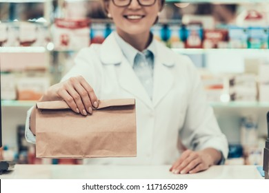 Closeup Pharmacist Holding Brown Bag with Medicine. Close up of Smiling Mature Woman Pharmacist wearing White Coat and Glasses Holding Drugs in Pharmacy. Professional Pharmacist in Drugstore