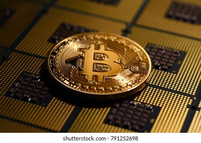 closeup of phisical bitcoin over computer cpu processors aligned. background and concept image.