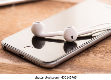 closeup phone and earbud on wood table