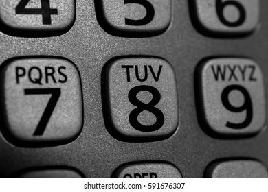 Closeup of phone number and letter buttons on cordless device, metallic gray and black