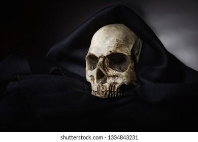 Closeup photo af old skull covered in black robe