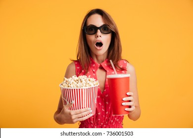 Close-up photo of amazed beautiful young woman in 3d glasses holding cola and popcorn and looking camera, isolated on yellow background