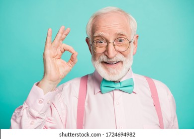 Closeup photo of amazing grey haired grandpa showing okey symbol express agreement wear specs pink shirt suspenders bow tie isolated bright teal color background