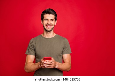 Closeup photo of amazing guy holding modern telephone hands casual outfit isolated on bright red background