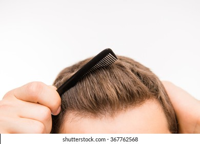 Close-up photo of a amn brushing his hair