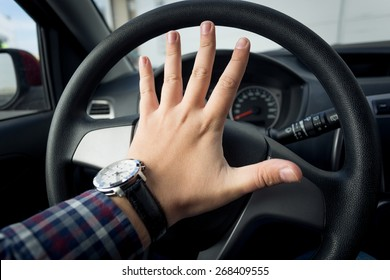 Closeup photo of angry driver honking in traffic