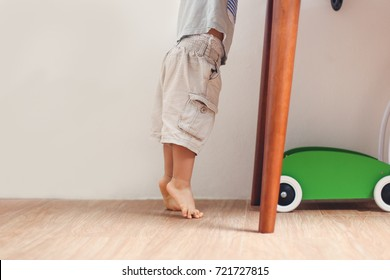 Closeup photo of Asian 18 months / 1 year old toddler baby boy child standing on tiptoes floor at home, Kid reaching up for things on the table - Soft & Selective focus