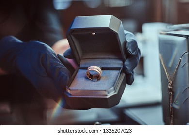 Close-up photo of assistant's hands who holds the box with the exclusive gold ring in a luxury jewelry store