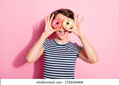 Closeup photo of attractive funny lady hold hands two sweet baked donuts like specs near eyes good mood wear casual white blue t-shirt isolated pastel pink color background