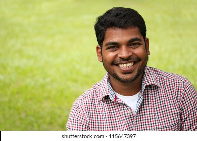 Closeup photo of attractive, handsome & smart south-asian/indian entrepreneur with smiling expression. The person is wearing a formal shirt & the picture is shot with beautiful lawn in the background