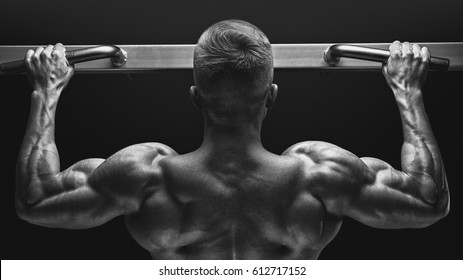 Close-up photo of attractive muscular bodybuilder guy doing pullups in gym. Fitness man pumping up lats muscles. Bodybuilding and fitness training health lifestyle concept
