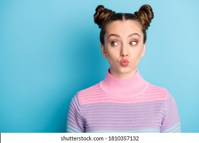 Closeup photo of attractive teen lady two funny buns good mood charming cute nice youngster look side empty space sending air kisses wear casual warm sweater isolated blue color background