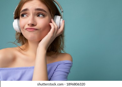 Closeup photo of attractive thoughtful young blonde woman wearing blue crop top isolated over blue background wall wearing white wireless bluetooth headphones listening to cool music and having fun