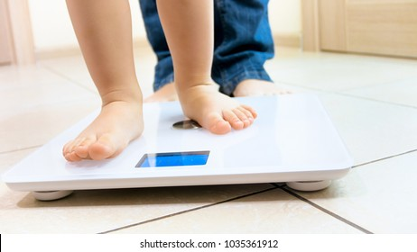 Closeup photo of baby's feet standing on digital weight scales