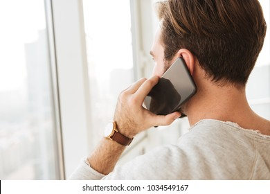 Closeup photo from back of man with short dark hair looking through window while having mobile call on black cell phone