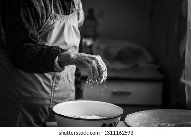 Closeup photo of baker making dough for bread. Hands of an old woman at work with the dough. Retro look.  Black and white photo of the hands of a woman