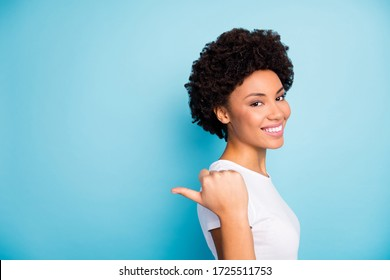 Closeup photo of beautiful dark skin curly lady sales manager indicating thumb finger side empty space sale prices shopping wear casual white t-shirt isolated blue color background