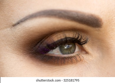 Closeup photo of beautiful female eye with grey pupil which reflects sky and evening makeup of brown eyeshadow black eyeliner mascara with violet tint and neat eyebrow, horizontal picture