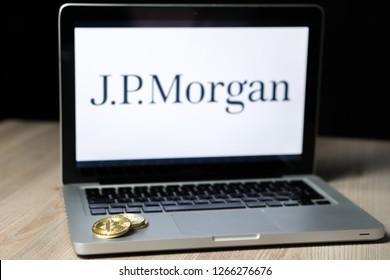 Closeup photo of Bitcoin coin with the J.P. Morgan logo on a laptop screen behind the coin
