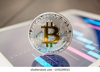 close-up photo of bitcoin cryptocurrency physical coin on the tablet computer showing stock market charts. trading bitcoin cryptocoin concept on the wooden table