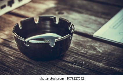 closeup photo of a black ashtray on a wooden table