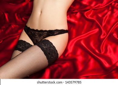 Closeup photo of black lingerie on red silk