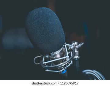 closeup photo of a black microphone in a garage studio