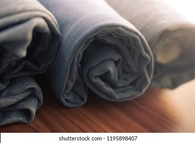 closeup photo of blue jeans rolled on a wooden table
