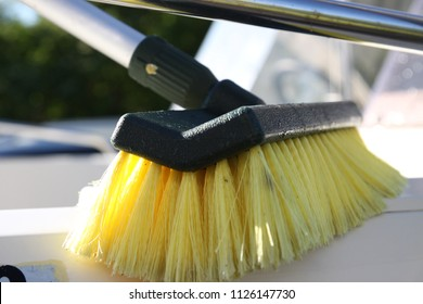 Close-up photo of boat cleaning with yellow brush