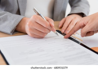 closeup photo of business people signing deal contract document.