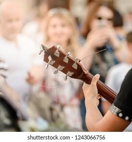 Closeup photo of busker plaing guitar on city street