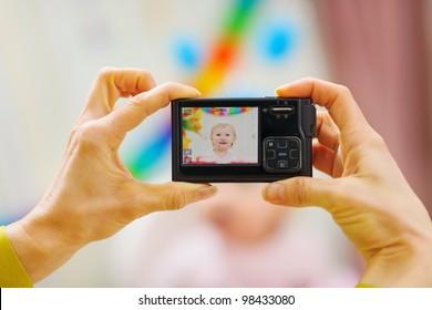 Closeup photo camera on mothers hands making birthday photos