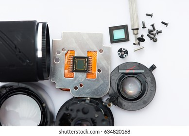 Close-up of photo camera parts dissassemble on white background view from above