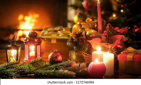 Closeup photo of candles and lanterns on wooden table in living room
