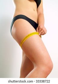 Closeup photo of a Caucasian woman's leg. She is measuring her thigh with a yellow metric tape measure after a diet.