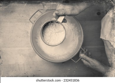 Closeup photo of a chef lady sifting flour for kneading. Black and white, directly above