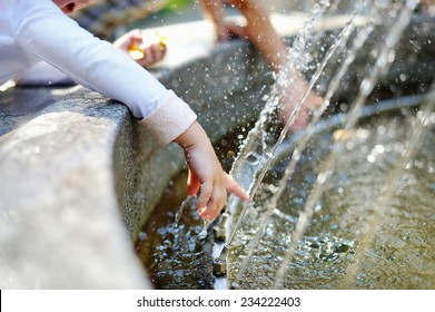 Closeup photo of child washing hands in a city fountain