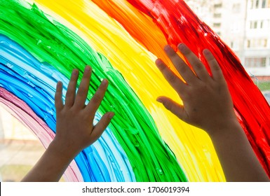 Close-up photo of child's hands touch painting rainbow on window. Family life background. Image of kids leisure at home, safety joy symbol. Chase the rainbow flashmob