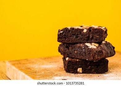 Closeup photo of the chocolate brownies with the sliced almond sprinkling on top on wooden tray with yellow background. The homemade easy bake oven cake.