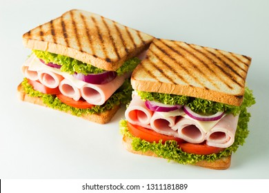 Close-up photo of a club sandwich. Sandwich with meat, prosciutto, salami, salad, vegetables, lettuce, tomato, onion and mustard on a fresh sliced rye bread on wooden background. Olives background.