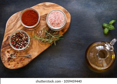 Close-up photo of colored dried spices in bowls on wooden board on black concreted table background with olive oil in jar
