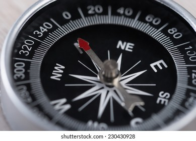 Closeup photo of compass on wooden table