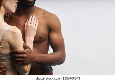 Close-up photo of couple body and hands, hug each other. Strong muscles of african man. Woman holding hand on his chest