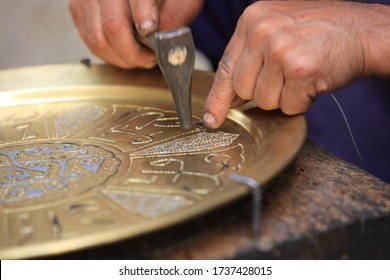 Closeup photo of craftsman's hands holding small hammer and working with traditional bronze plate decorated by silver ornament at the market of Medina old town in Tunis, Tunisia