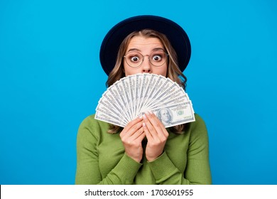 Closeup photo of crazy funny curly lady hold fan dollar bucks rich person freelance salary hide mouth face expression wear specs hat green turtleneck isolated blue color background