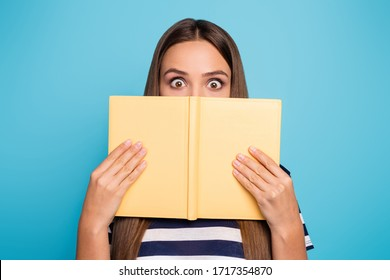 Closeup photo of crazy pretty lady hold planner copybook diary hiding half facial expression shy person big eyes book worm wear striped t-shirt isolated blue color background