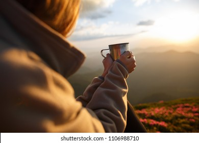 Closeup photo of cup with tea in traveler's hand over out of focus mountains view. A young tourist woman drinks a hot drink from a cup and enjoys the scenery in the mountains. Trekking concept