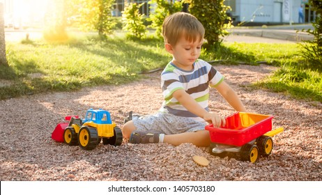 Closeup photo of cute little boy playing on the palyground with toys. Child having fun with truck, excavator and trailer. He is pretending to be a builder or driver